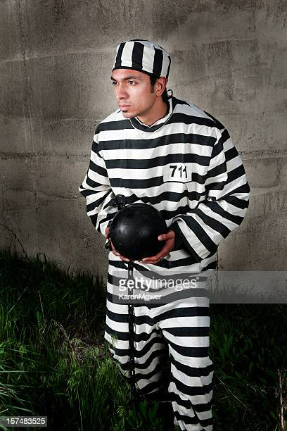 prisoner in black and white stripes holding a ball & chain - prisoner stock pictures, royalty-free photos & images
