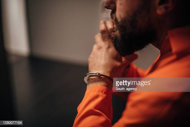 prisoner in orange jumpsuit sitting in prison visiting room - prisoner stock pictures, royalty-free photos & images