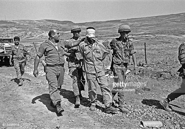 A prisoner is blindfolded and lead by troops as part of the Israeli advance into Syria during the SixDay War