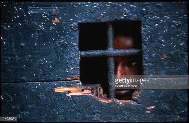A prisoner looks out a small window May 4 1993 in Mogadishu Somalia Following the departure of US forces UN troops continue the humanitarian...