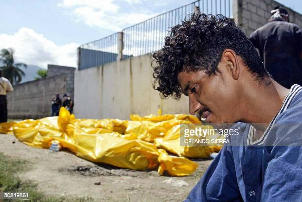 A prisoner mournes next to the bodies of 103 inmates who were killed when a fire raged through a Honduran prison in the town of San Pedro Sula some...