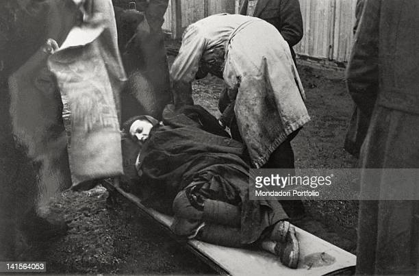 A prisoner officer is lying down on a stretcher after he has fainted from hunger and cold during the daily rollcall He is being assisted by other...