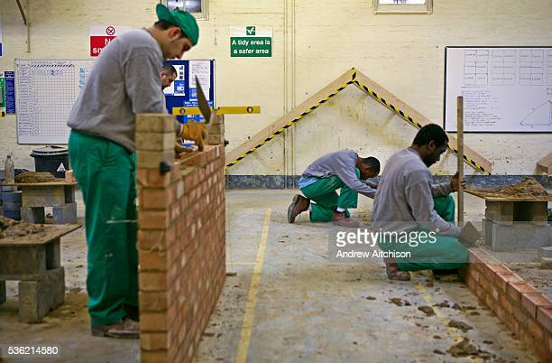 A prisoner on a building course builds a brick wall inside the building workshop at Wandsworth prison HMP Wandsworth in South West London United...