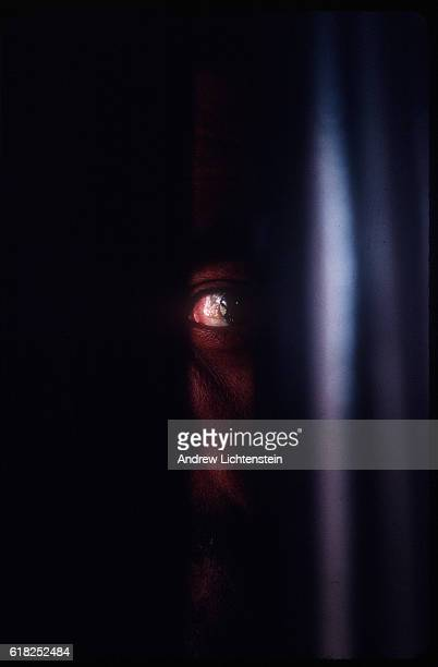 A prisoner peers out of his maximum security cell where he is kept in isolation 23 hours of every day at the Ferguson Unit in Midway Texas 1997