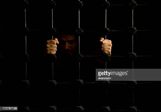 Prisoner pulling on bars with both hands in dark cell
