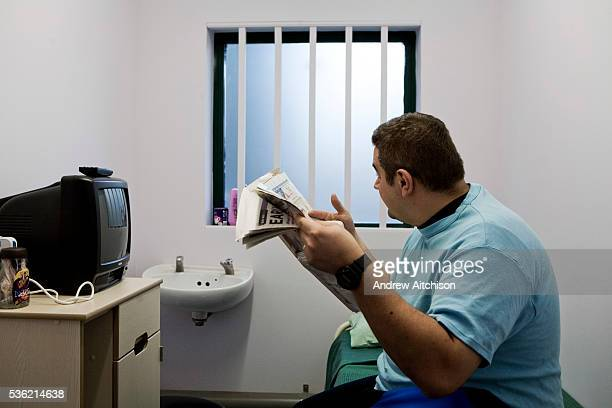 A prisoner reading a newspaper in his cell HMP Wandsworth London United Kingdom