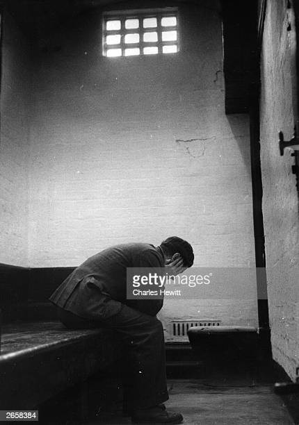 A prisoner sitting in his cell at a police station in Lancashire Original Publication Picture Post 7672 They Keep The Queen's Peace pub 1955