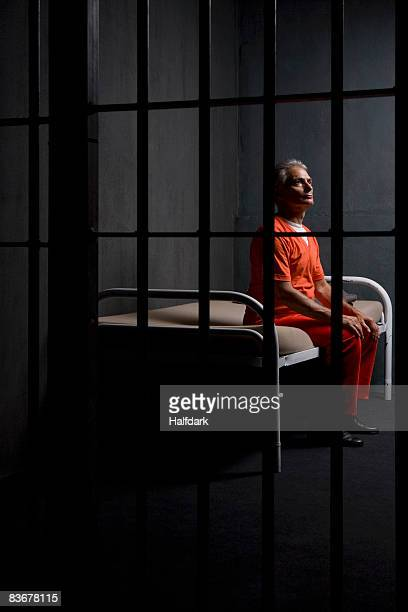 A prisoner sitting on a bed in a prison cell