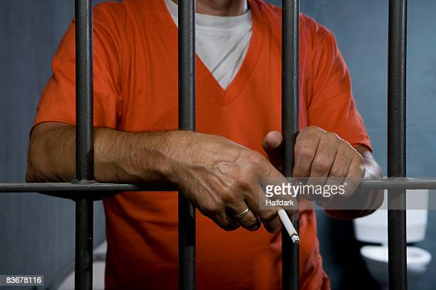 A prisoner smoking a cigarette in his prison cell