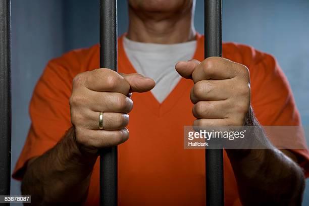 a prisoner standing behind prison bars - prisioneiro - fotografias e filmes do acervo