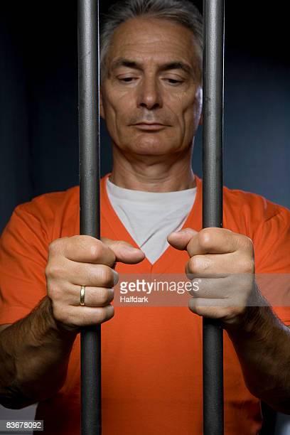 a prisoner standing behind prison bars - prisonnier photos et images de collection