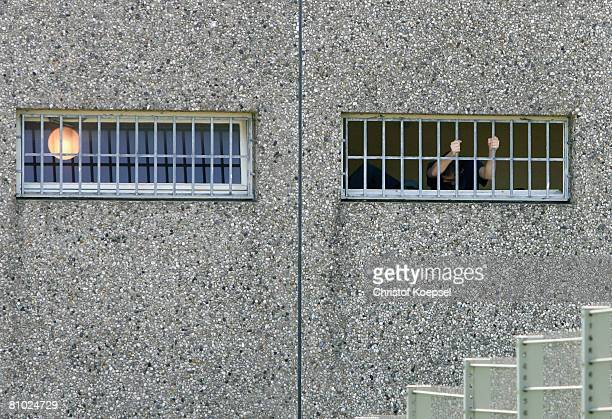 A prisoner stands at the grid at the JVA Iserlohn prison on May 8 2008 in Iserlohn Germany German Football Association U18 national coach Heiko...