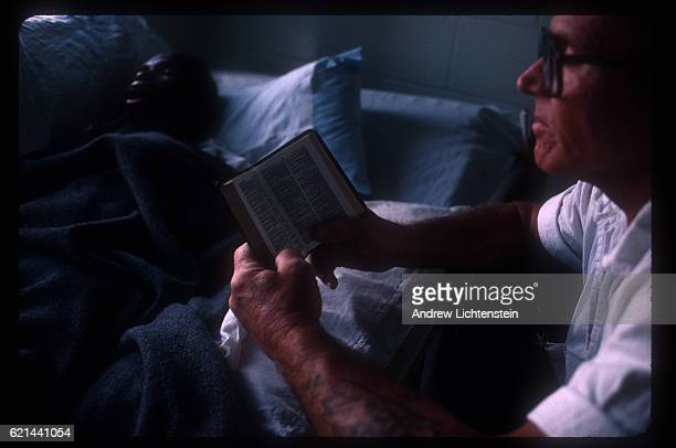A prisoner volunteer working in a special hospice wing of the Stiles Unit a Texas state prison in Beaumont reads to a fellow prisoner dying of AIDS...