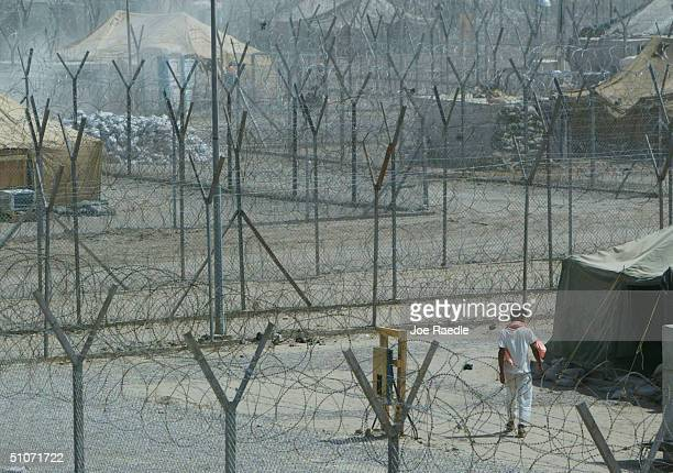 A prisoner walks near a tent where he is housed in the Abu Ghraib prison July 15 2004 west of Baghdad Iraq Many of the prisoners were picked up by US...