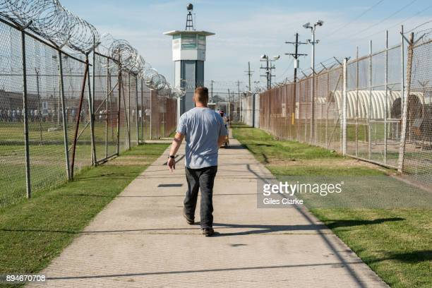 A prisoner walks thru a fenced section toward a guard tower at Angola Prison The Louisiana State Penitentiary also known as Angola and nicknamed the...