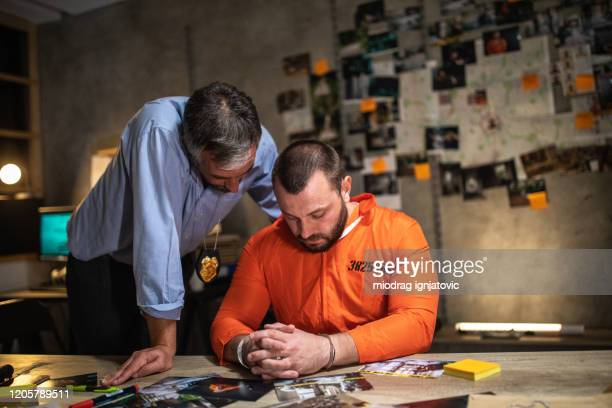 prisoner with handcuffs being interviewed in interrogation room - confession law stock pictures, royalty-free photos & images