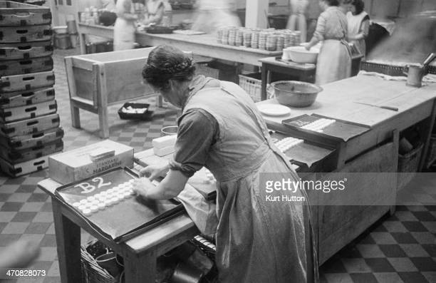 A prisoner working in the kitchens at Holloway Prison north London March 1947 She is arranging pats of margarine on a tray for BWing Each cell will...