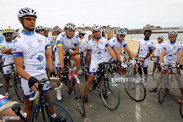 Prisoners and jailers listen to a briefing prior to take the start of the Transpyreneenne bicycle racing on September 17 2012 in Ciboure southwestern...