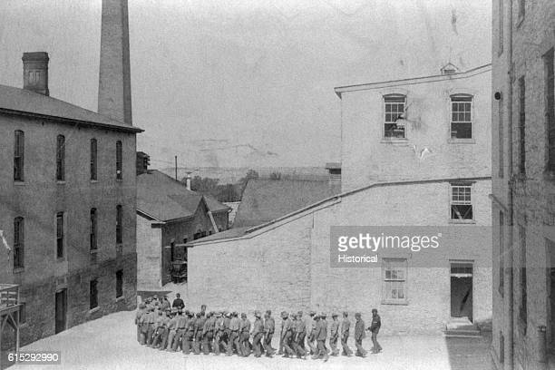 Prisoners at Fort Leavenworth Penetentiary march in a line to the mess hall for dinner ca 1890s