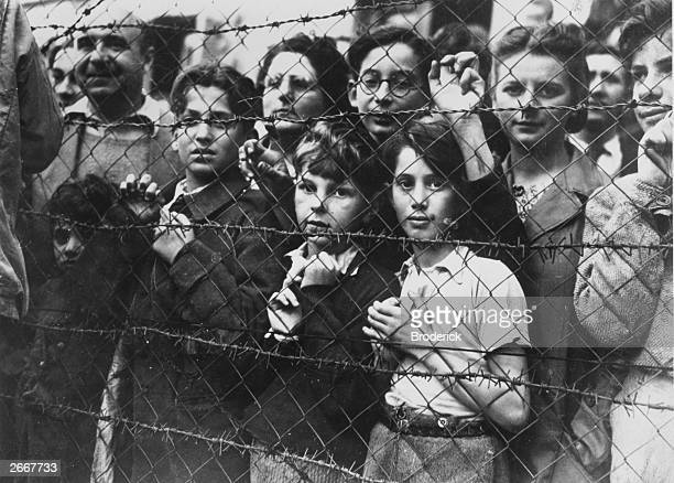 Prisoners at the Vittel concentration camp peering through the fence after the town was captured by the Third Army and their liberation secured.