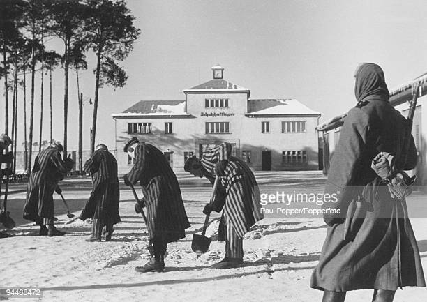 Prisoners clear away snow from the entrance to Sachsenhausen concentration camp in Oranienburg Germany February 1941 The sign above the entrance...