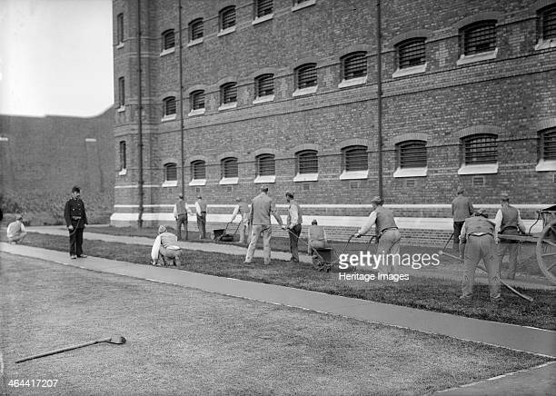 Prisoners cutting grass at Wormwood Scrubs prison London c19001950 Various parts of the 'Scrubs' were built using prison labour between 1874 and 1891...