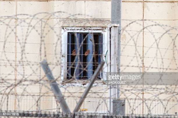 Prisoners gesture from their cell at HaSharon high security prison, some 40 kilometers northeast of Tel Aviv, on February 23 after an...