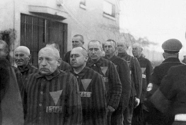 Prisoners in striped uniforms bearing triangular badges, on parade in Sachsenhausen Concentration Camp near Berlin, Germany, 19th December 1938. Nazi...