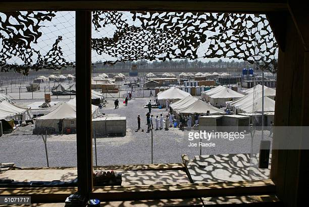 Prisoners mill around in a common area where they are housed in tents in the Abu Ghraib prison on July 15 2004 west of Baghdad Iraq Many of the...