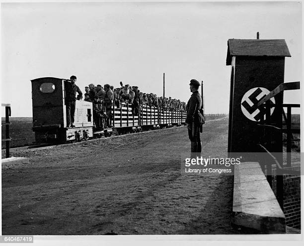 Prisoners of war are packed into a train that will take them to the work site while a German guard looks on | Location Land Niedersachsen Germany