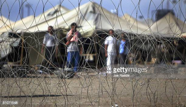 Prisoners stand next to the tents in which they are housed at the Abu Ghraib prison on July 15 2004 west of Baghdad Iraq Many of the prisoners were...