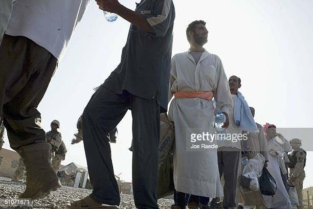 Prisoners wait to board a bus as they are released from Abu Ghraib prison on July 15 2004 west of Baghdad Iraq The US army released 65 prisoners that...