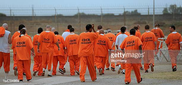 Prisoners walk a lap in a recreation yard at Deuel Vocational Institution in Tracy California US on Thursday Oct 11 2012 The primary purpose of the...