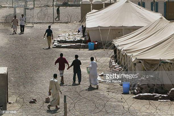Prisoners wander by their housing in the Abu Ghraib prison July 15 2004 west of Baghdad Iraq Many of the prisoners were picked up by US troops during...