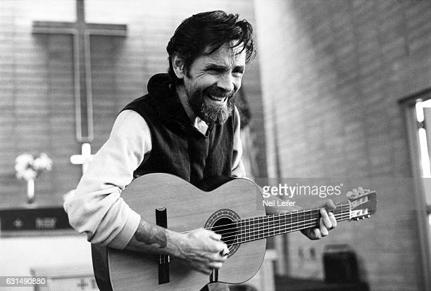 The Inmate Nation Portrait of Charles Manson playing guitar in chapel during photo shoot at California Medical Facility Vacaville CA CREDIT Neil...