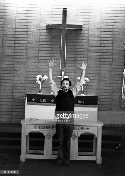 The Inmate Nation Portrait of Charles Manson posing in front of altar and cross in chapel during photo shoot at California Medical Facility Vacaville...