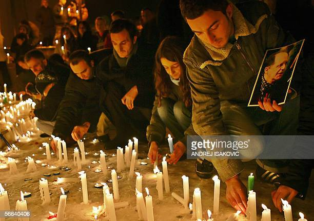 An ethnic Albanian man holds a picture of the late Kosovo President Ibrahim Rugova as hundreds light candles in the centre of Pristina 21 January...