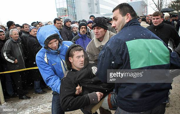 Kosovo Albanians carry a faintedfit man as thousands wait to pay their last respects to the late Kosovo President Ibrahim Rugova in Pristina 23...