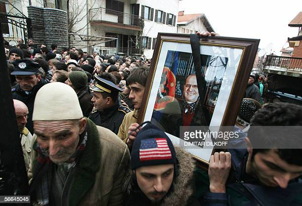 Men hold a picture of the late Kosovo President Ibrahim Rugova as thousands of Kosovo Albanians wait in line to pay their respect in front of his...