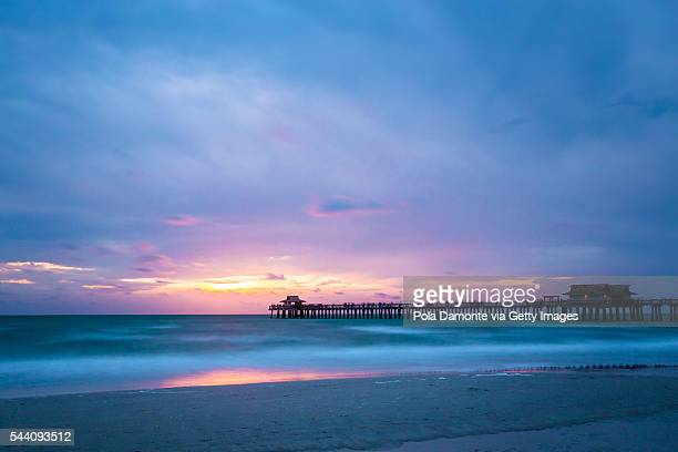 Pristine and idyllic beach sunset, with a blue sky in Naples Pier, Florida, USA