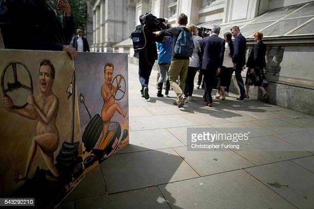 Priti Patel Minister of State for Employment is pursued by waiting media past political cartoons of Osborne and Cameron in Whitehall after a cabinet...