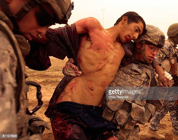 Private Aaron Livas a soldier with the 2nd Battalion 30th Infantry Regiment of the 10th Mountain Division helps carry a wounded Iraqi man during a...