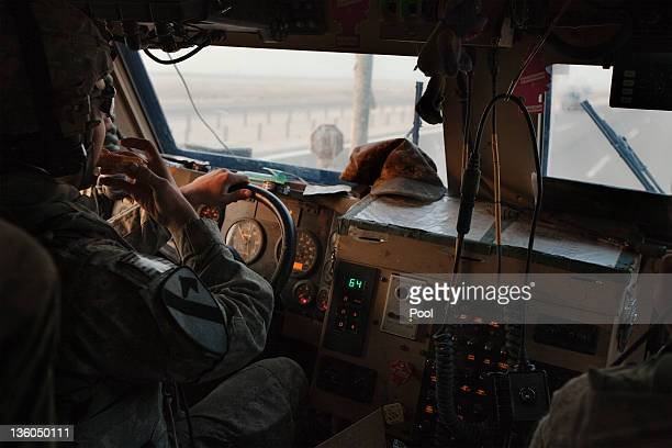 Private Adam Hendrix of the 3rd Brigade Combat Team 1st Cavalry Division eats a sandwich while driving a Mine Resistant Ambush Protected vehicle on...