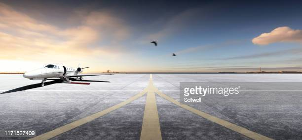 private aircraft parking on the tarmac, against sunset - airport tarmac stock pictures, royalty-free photos & images