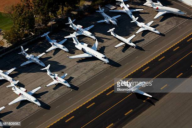 Private aircraft sit on the tarmac as an airplane taxis on the runway at Santa Monica Municipal Airport in this aerial photograph taken over Santa...