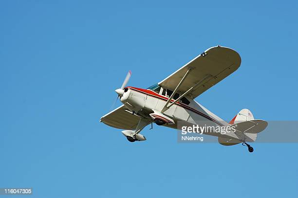 private airplane Fairchild M62A flying in clear blue sky