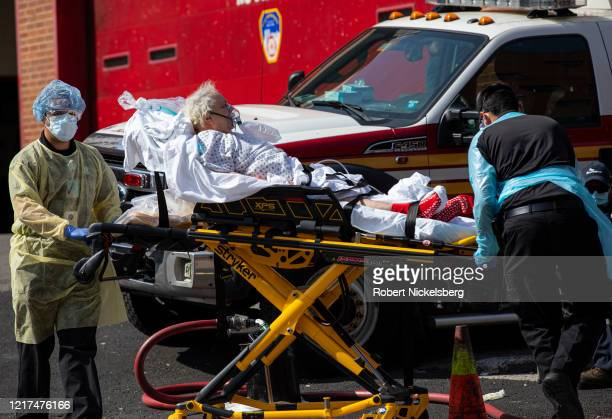 A private ambulance team transports out a probable COVID19 patient from the emergency room of the Elmhurst Hospital Center on April 7 2020 in the...