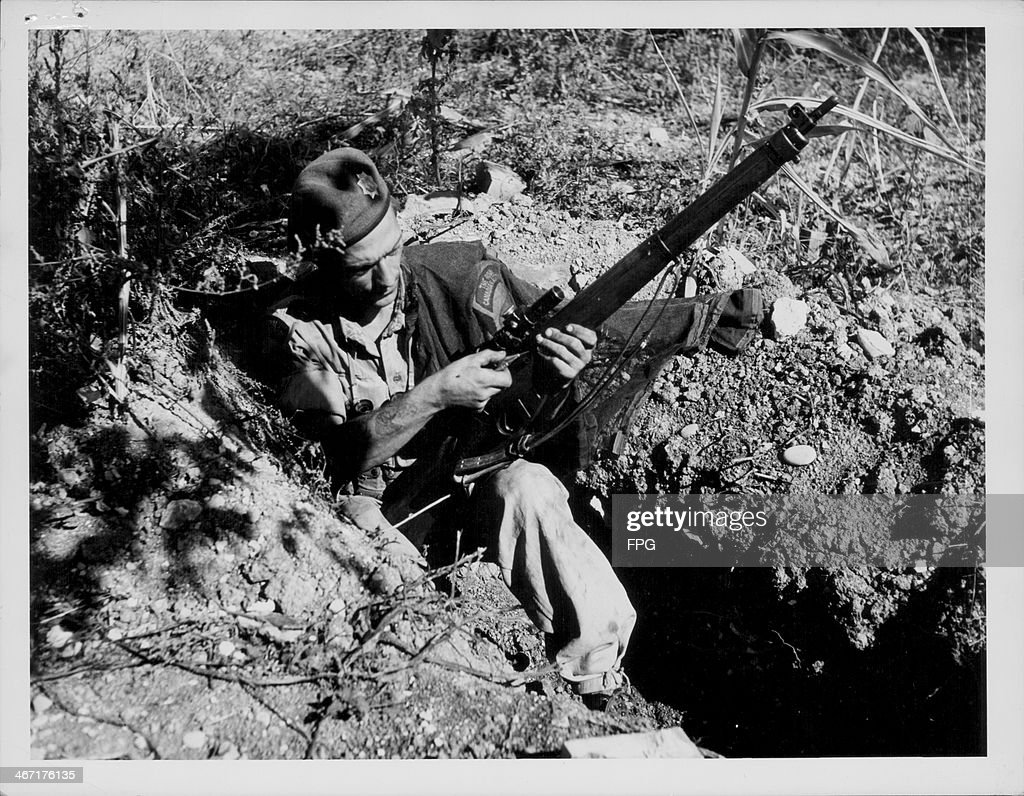 Private Bob Christopher of Ontario, in an abandoned German weapons