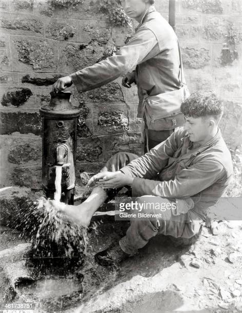 Private C. L. Scott of the 4th Infantry Division is washing his feet at a public fountain. 2nd August 1944. The city was liberated hours before by...