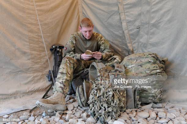 Private Curtis Welsby from Manchester of the 1st Battalion The Mercian Regiment takes a moment in Camp Bastion Afghanistan to read his Bible which...